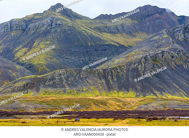 Car riding along Ring Road in front of mossy mountain, Borgarbyggd, Iceland