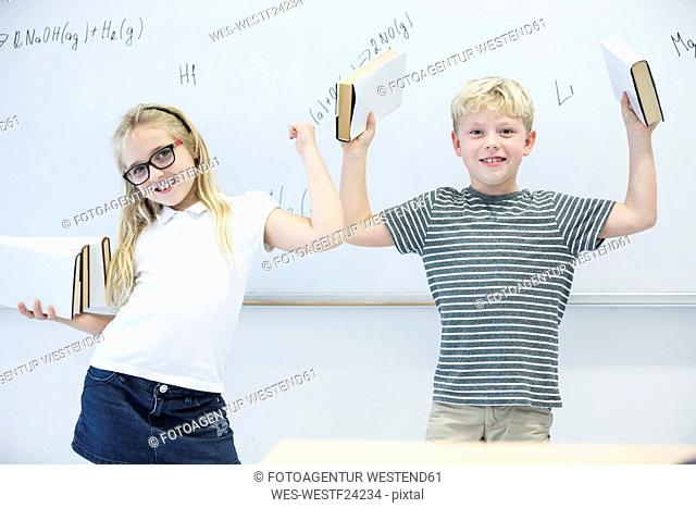 Portrait of happy schoolgirl and schoolboy carrying books in class