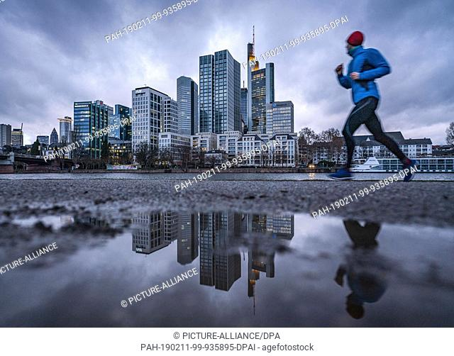 11 February 2019, Hessen, Frankfurt/Main: At dawn, a jogger runs past the skyline of a high-rise building on the Main River, which is reflected in a puddle