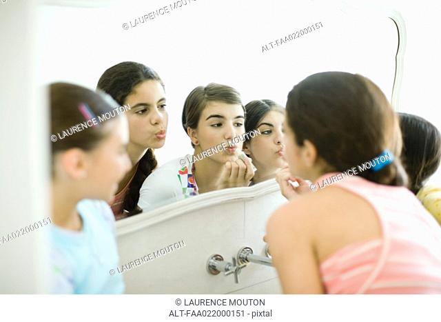 Young female friends looking at mirror, putting on make-up