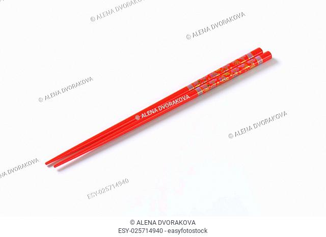 pair of red chopsticks on white background