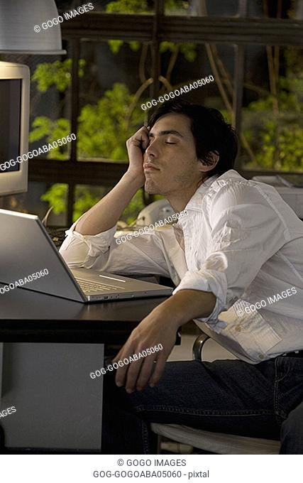 Businessman asleep before his laptop