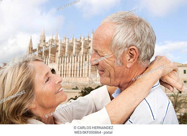 Spain, Mallorca, Palma, Senior couple smiling with Cathedral Santa Maria, portrait