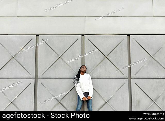 Young woman holding a tablet at a grey wall