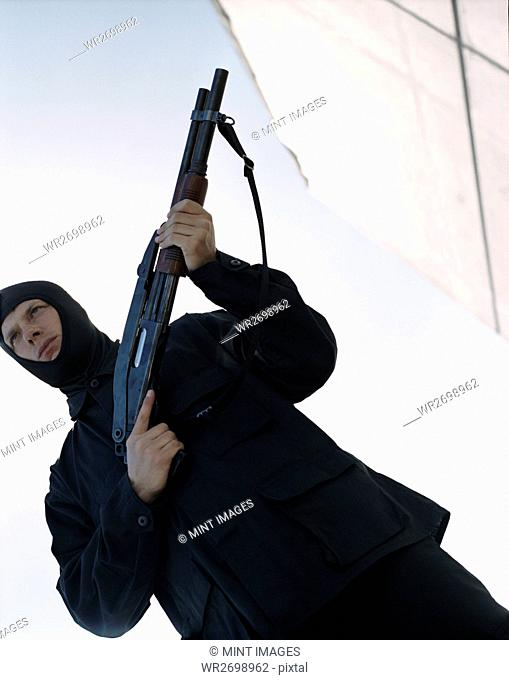 Man holding high powered shotgun, wearing special forces uniform and balaclava