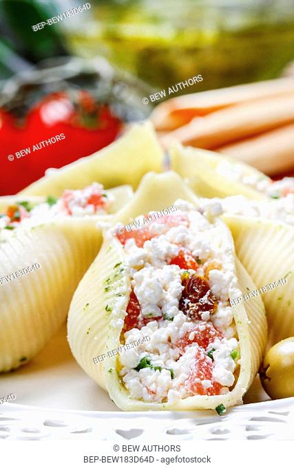 Italian cuisine: stuffed pasta shells and stack of breadsticks. Tomatoes and pesto sauce in the background