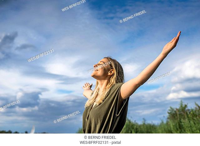 Smiling woman standing with outstretched arms outdoors