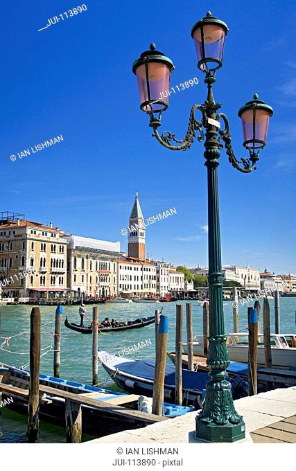 Streetlight and gondola on sunny Grand Canal in front of San Marco Campanile and architectural buildings in Venice, Italy