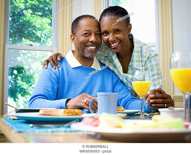 Portrait of a woman and a man smiling at the breakfast table