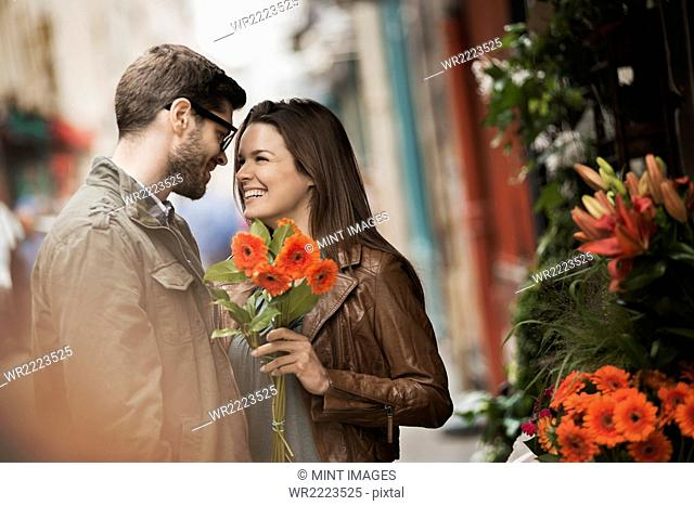 A man and woman by a flower stall in the city, holding a bunch of bright red flowers