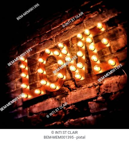 LOVE' sign lit up on brick wall