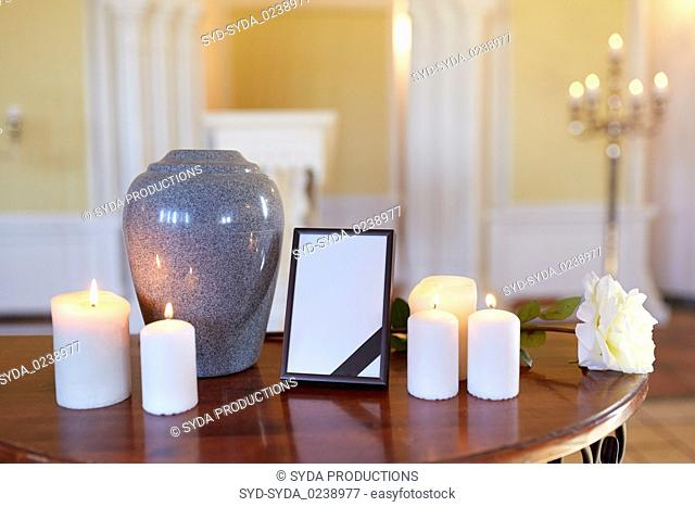 photo frame, cremation urn and candles in church