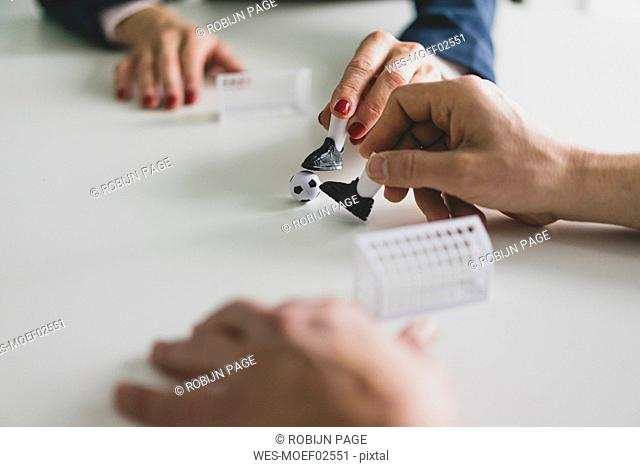 Close-up of businesswoman and businessman playing table football in office