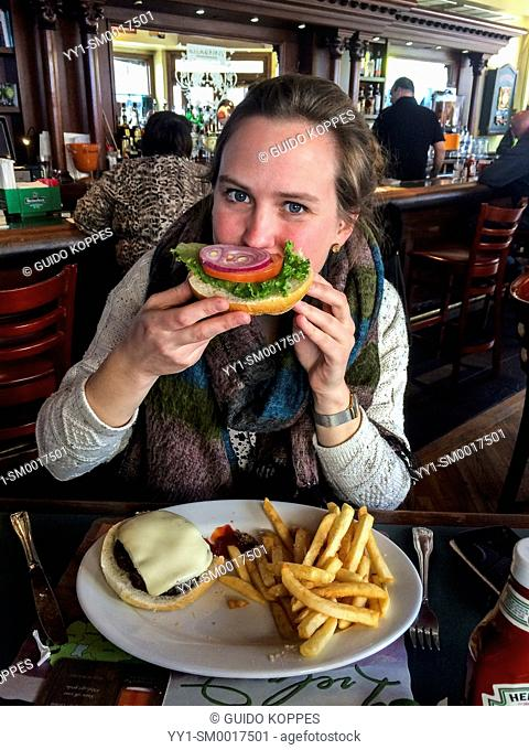 Newark, New Jersey, USA. Young, caucasian woman eating a huge hamburger