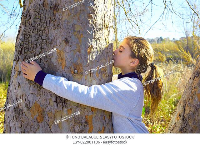 Kid girls loves nature hug annd kiss a tree tunk in outdoor winter park