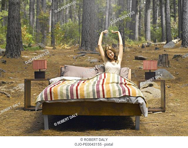 A woman stretching in a bed outdoors in the woods
