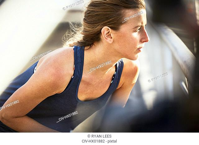Serious female runner stretching looking away