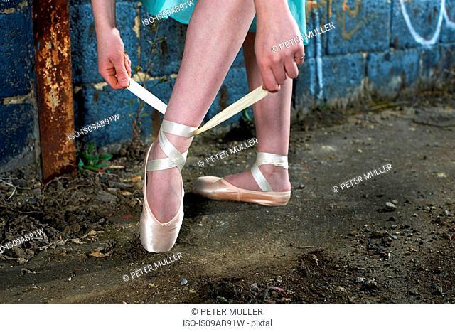 Ballet dancer tying ribbon on ballet shoe