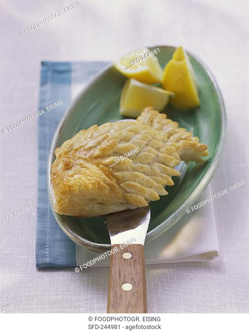 Puff pastry fish with wedges of lemon