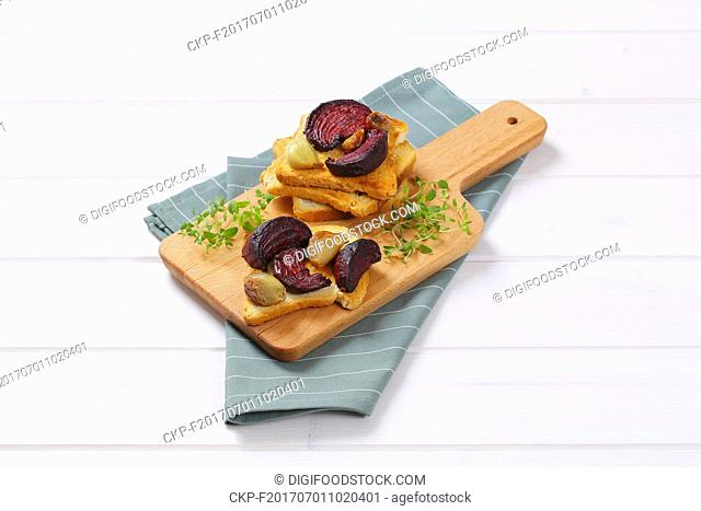 toast with baked beetroot, garlic and thyme on wooden cutting board