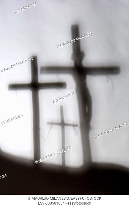 Three shadows of the crosses on the hill with Jesus on the first