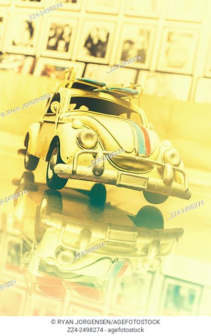 Collectible retro toy model car with surfboards on roof rack mirrored on glass display table. Automotive memorabilia
