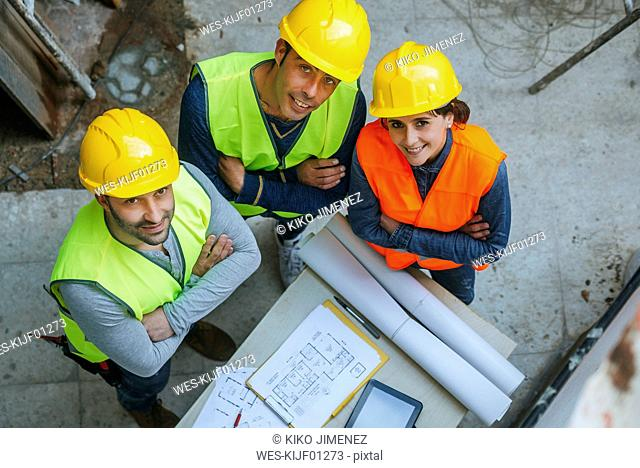 Portrait of smiling woman and two men in workwear with construction plan