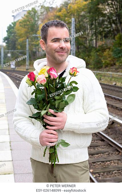 handsome man waiting at train station with roses