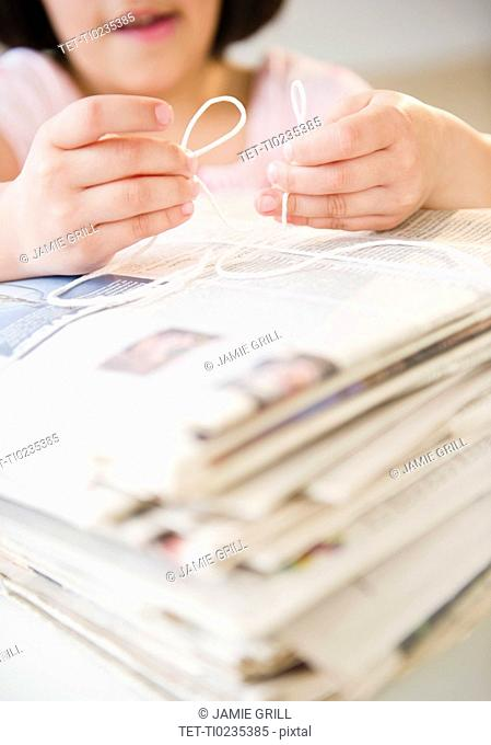 Girl's 8-9 hands tying pile of newspapers with string