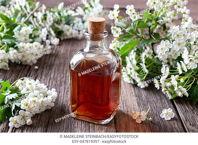 A bottle of herbal tincture with hawthorn flowers