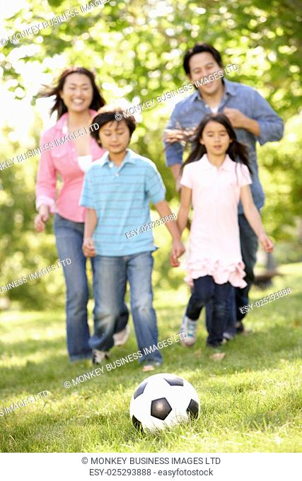 Asian family playing soccer in park