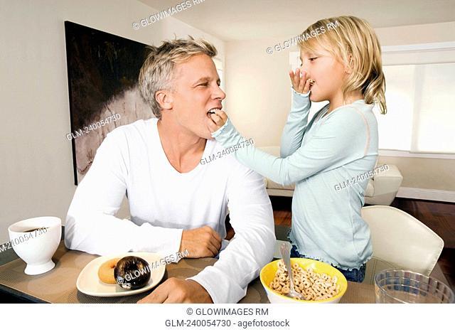 Man and his daughter having breakfast