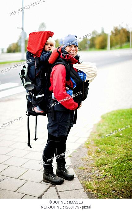 Woman carrying two children in backpack