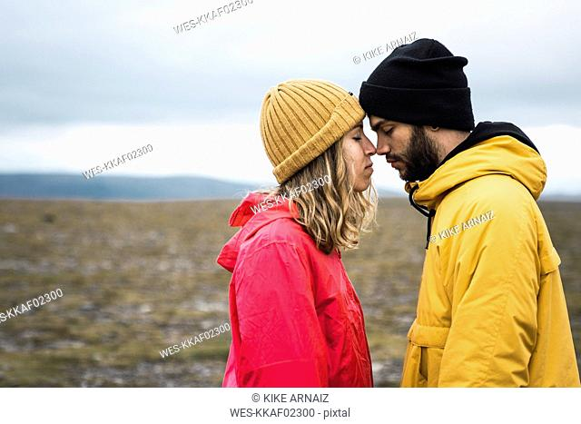 Young couple rubbing affectionately noses, Lapland, Norway