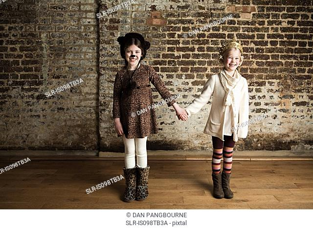 Young girls dressed up as cat and queen, holding hands