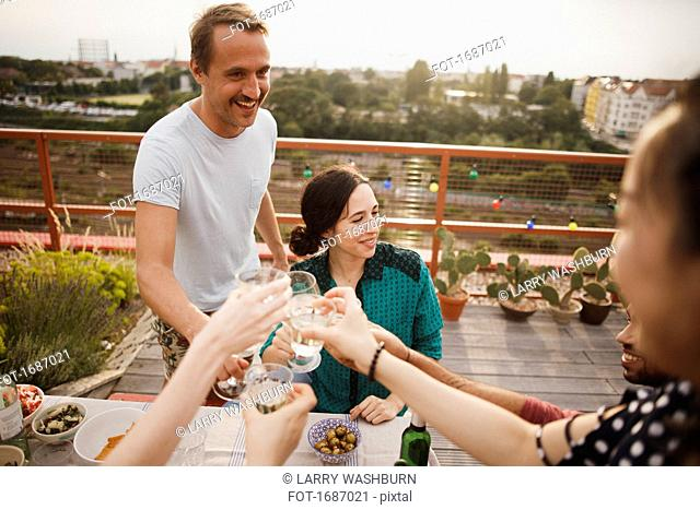 Happy male and female friends toasting wineglasses on patio