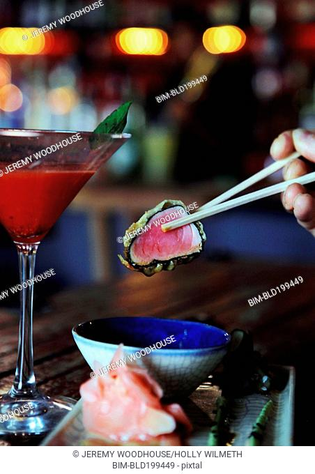 Person eating tuna sushi in restaurant
