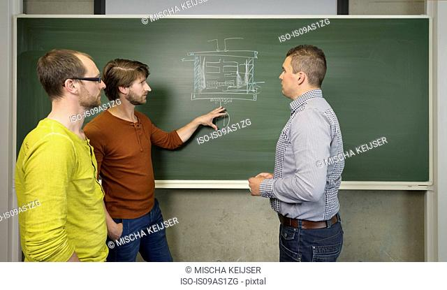 Three mid adult men, discussing ideas at a hightech startup company