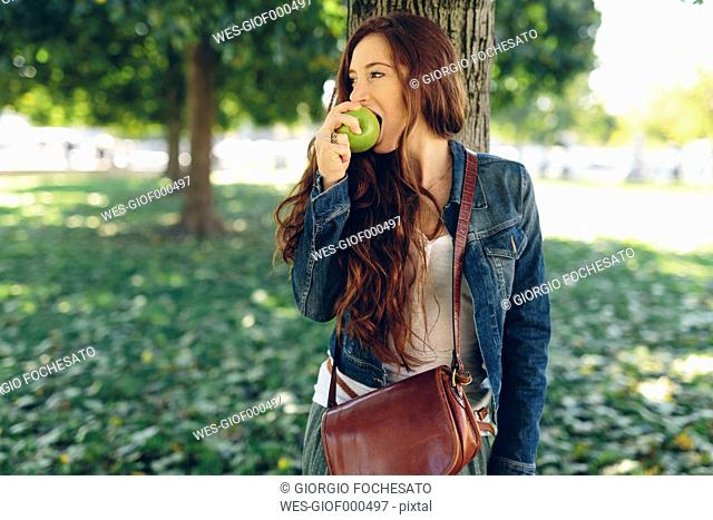 Woman eating an apple in park