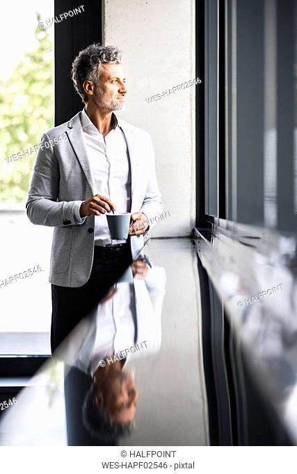 Smiling mature businessman with coffee mug looking out of window