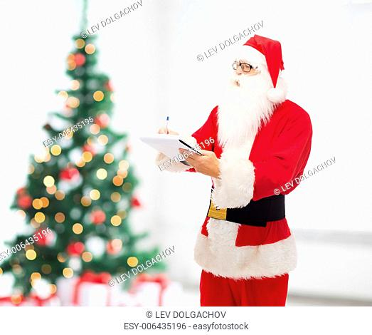 christmas, holidays and people concept - man in costume of santa claus with notepad and pen over living room and tree background