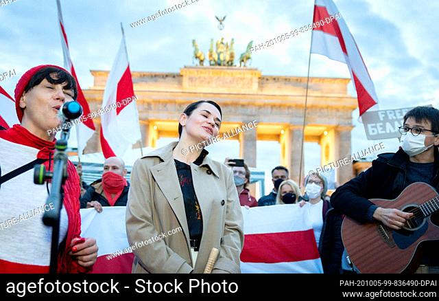 05 October 2020, Berlin: Opposition leader Svetlana Tikhanovskaya from Belarus sings a song with her supporters at the Brandenburg Gate
