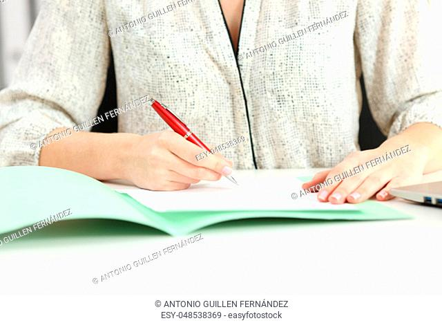 Front view close up portrait of a businesswoman hands signing a contract on a desktop