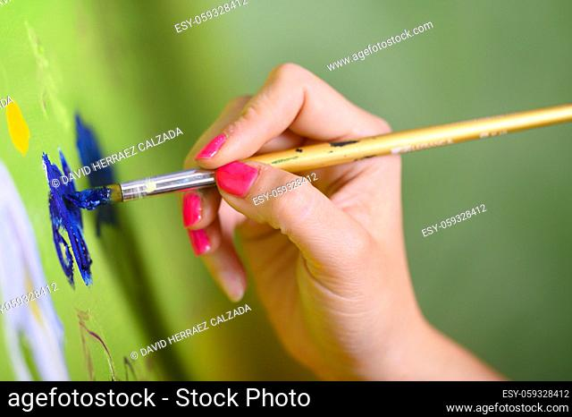 Close-up Shot of Female Artist Hand, Holding Paint Brush and Drawing Oil Painting. Contemporary Painter Creating Modern Abstract Piece of Fine Art
