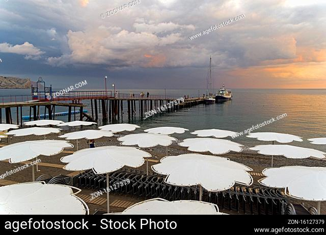 View of evening sunset sky from the empty beach of the resort town of Sudak. Crimea