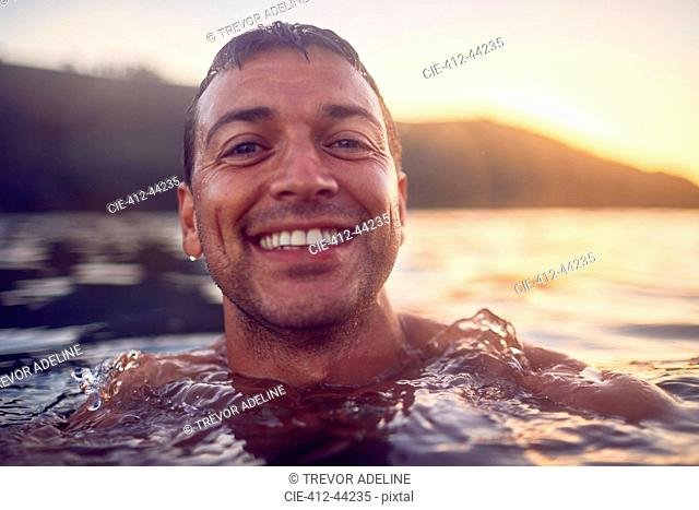 Close up portrait smiling, carefree man swimming in ocean