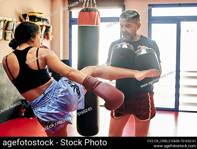 Young woman training with her Muay Thai trainer in a gym