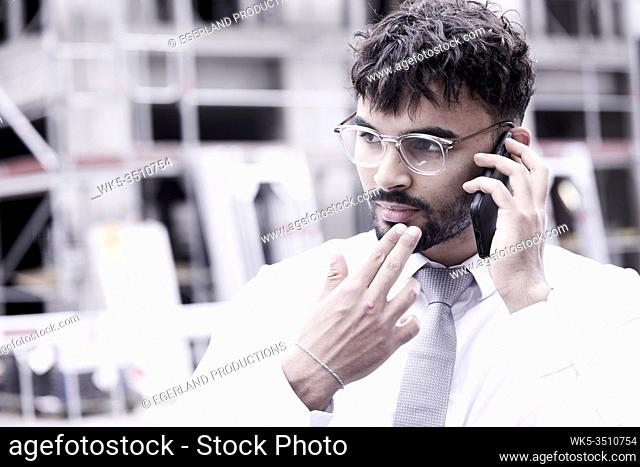 doubtful businessman on building site, talking on phone