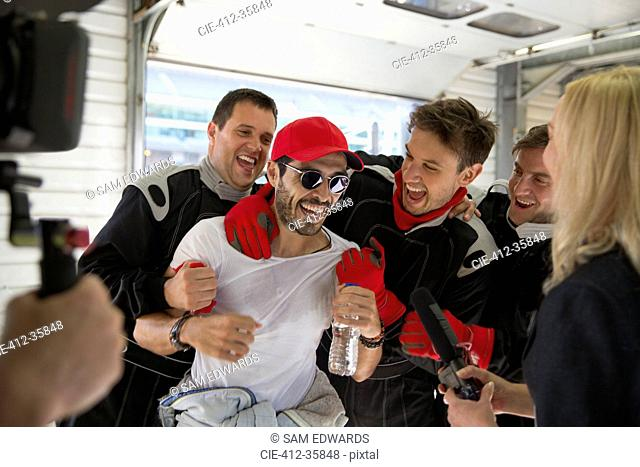 Formula one driver and team celebrating victory in repair garage