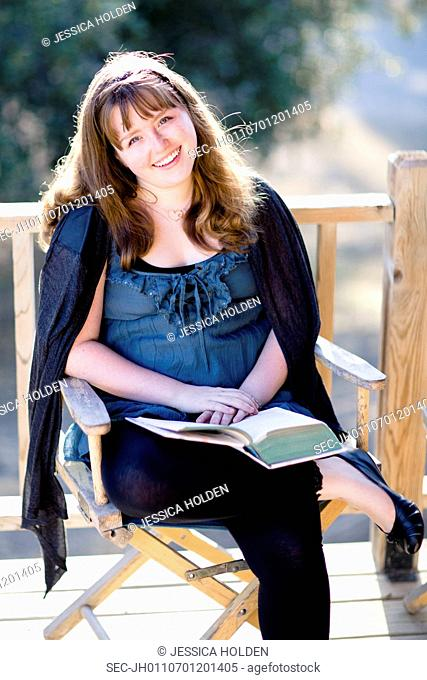 Portrait of teenage girl (13-15) with book on porch